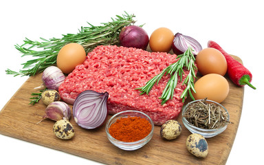 minced meat of beef and different foods closeup. white backgroun