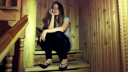 nice teen girl speaks by mobile phone sitting on wooden stairs