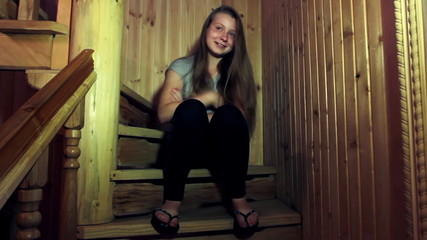 nice teen girl sits and smiles on wooden stairs in home
