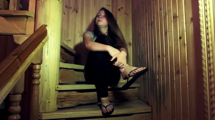 nice teen girl sits sad and hugs leg on wooden stairs in home