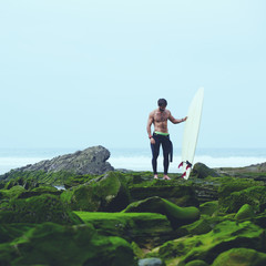 Professional surfer in black wetsuit standing on moss rocks