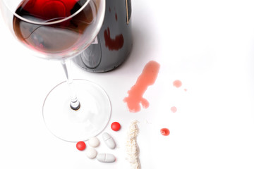 A glass of red wine with bottle and drugs on a white background