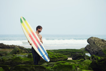 Young surfer carrying surfboard standing on moss rocks