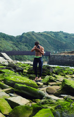 Beautiful surfer with muscular body taking picture with camera