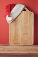 Christmas background with cutting board and Santa hat