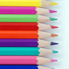 multicolored crayons in a row on white background