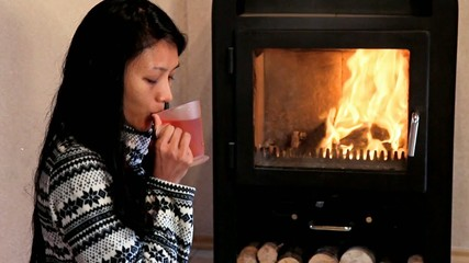 Young woman drinking tea by the fire