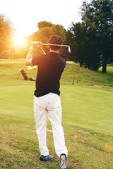 Golfer swinging his driver and looking away playing at sunset