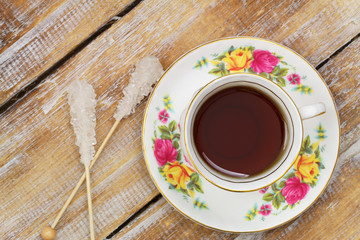 Tea in vintage cup and sugar sticks on wooden surface