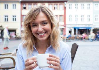 Lachende Frau mit blonden Locke im Strassencafe