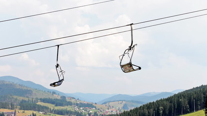 empty mountain lift moves up and down in mountains, closeup