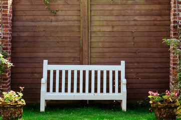 White Wooden garden bench in English garden, color filter