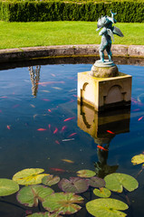 English Landscape garden in Summertime with fishpond and statue