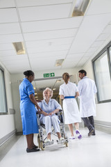 Senior Female Patient in Wheelchair & Nurse in Hospital