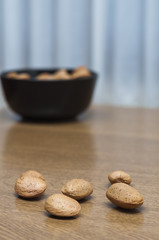 Almonds on a black bowl on wooden background