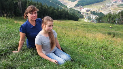 mother with daughter sit on green grass mountain at Carpathian