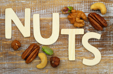 Word nuts written with wooden letters with selection of nuts