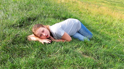 young girl lies on really green grass in mountains
