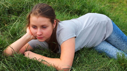 young girl lies on really green grass in mountains, closeup