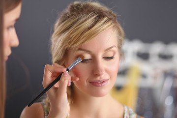 Artist doing professional make up of woman
