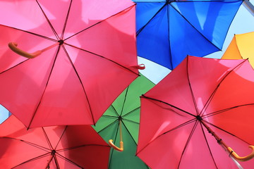 many bright umbrellas against sky
