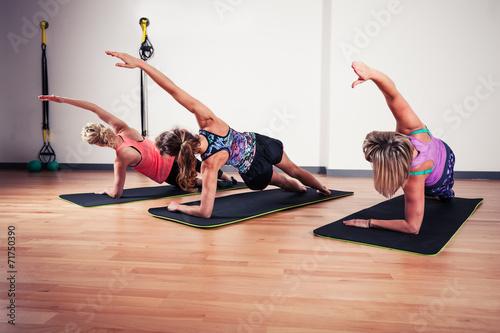 Fototapeta Women stretching in the gym