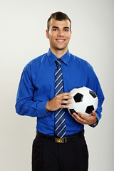 Young businessman holds a soccer ball on gray background