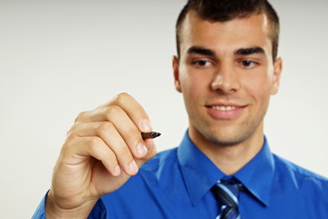 Young businessman writes with marker, focus is on marker