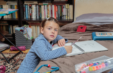 fashionable little girl sitting in her room and doing home work