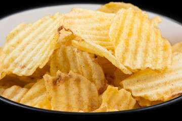 Yellow ribbed potato chips in a black bowl with a white inside