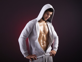 Handsome fitness man showing six pack abs on a dark background