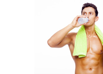Fitness man drinking a bottle of water, isolated on white backgr