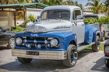 Blue, grey classic vintage pickup truck standing in garden