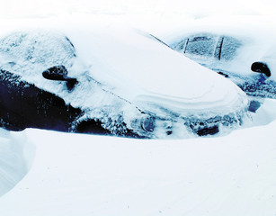 Snow covered frozen car at winter