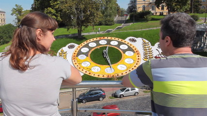 couple have rest in Kiev near real flower clock, back view