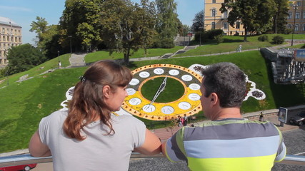 couple stand and talk in Kiev near real flower clock, back view
