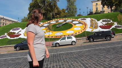 pretty woman looks at hour on real flower clock in Kiev