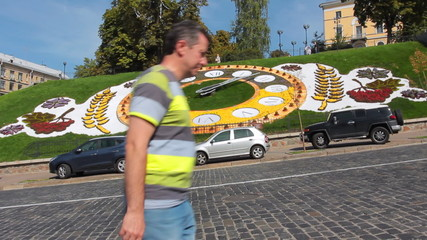 man goes and looks at hour on real flower clock in Kiev
