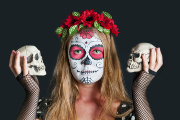 Young girl with Calavera Mexicana makeup mask and with skulls