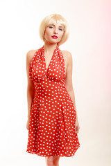 Portrait beautiful pinup girl in blond wig retro red dress