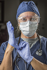 Concerned Female Doctor or Nurse Putting on Protective Facial We