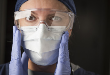 Female Doctor or Nurse Putting on Protective Facial Wear