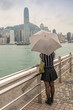 Asian girl with umbrella mesmerized by Hong Kong panorama