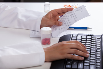Pharmacist checking information about medicines