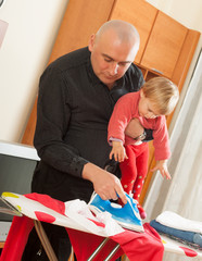man holding his daughter and ironing