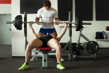 Image of two athletes exercising with barbell