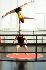 Strong man doing acrobatic rack with his partner