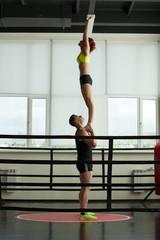 Strong acrobat holding his slender partner in gym