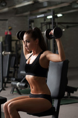 Sporty girl exercising with dumbbells in gym
