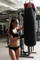 Beautiful brunette posing with punching bag